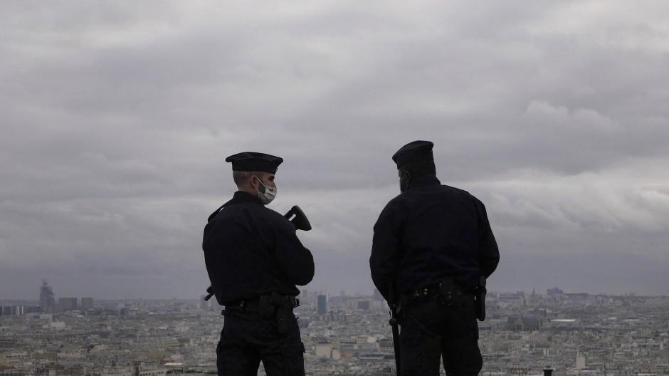 Zwei Polizeibeamte stehen auf dem Vorplatz der Basilika Sacré-Coeur auf dem Montmartre in Paris Wache.