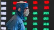 Ein Mitarbeiter steht an der Schanghaier Börse in Schutzkleidung vor einem Monitor mit Kursentwicklungen .