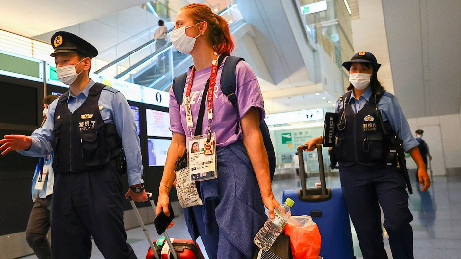 Die belarussische Sprinterin Kristina Timanowskaja mit zwei Polizisten am Sonntag im Flughafen in Tokio