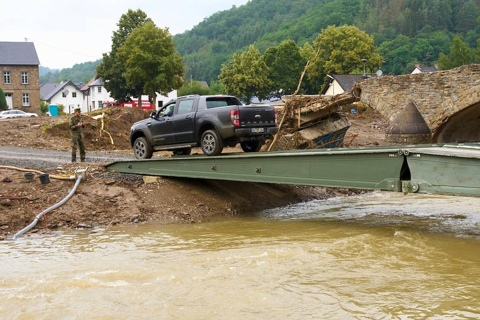 Ein Geländewagen überquert am Samstag die Ahr auf einer Behelfsbrücke, die die Bundeswehr gebaut hat.