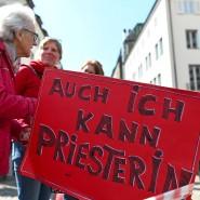 """Teilnehmerinnen einer Protestaktion der Initiative Maria 2.0 halten in Freiburg vor dem Münster im Mai 2019 ein Plakat mit der Aufschrift """"Auch ich kann Priesterin""""."""