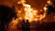 In Portugal versuchen Feuerwehrleute die Flammen unter Kontrolle zu bekommen.