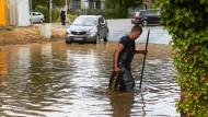 Ein Feuerwehrmann in einer überfluteten Bahnüberführung im Rheintal