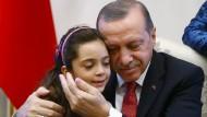 So inszeniert er sich gern: Der türkische Staatspräsident Recep Tayyip Erdogan mit einem siebenjährigen syrischen Mädchen, das Tweets aus Aleppo sendete und flüchten konnte.