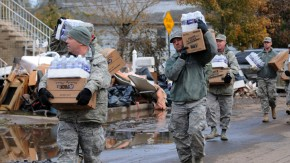 New York Air National Guard Master Sgt. Thomas Moade leads other members of the 174th in taking water and cases of food to local residents in Staten Island in this handout photo