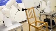 """Die beiden Roboterarme bauen den Ikea-Stuhl """"Stefan"""" selbständig zusammen."""