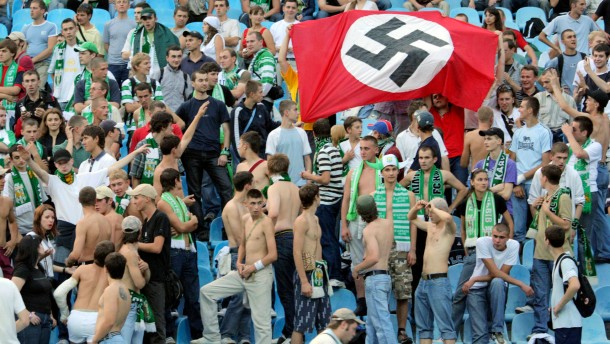 Supporters of Karpaty Lviv hold a German Nazi flag with a swastika as they attend a soccer match against Dynamo Kiev in Kiev