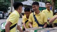 """""""Auf dem Boden geblieben"""": Die Jungen und ihr Trainer (Mitte) bereiten Ende Juni Essen für eine Zeremonie anlässlich ihrer Rettung vor einem Jahr vor."""