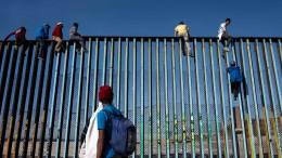 Erste Flüchtlinge klettern auf Grenzzaun