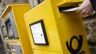 Eine Frau wirft in Erfurt einen Brief wird in einen Briefkasten der Deutschen Post AG.