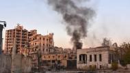 Rauch steigt über der Bustan-al-Basha-Nachbarschaft in Aleppo auf. Die syrische Regierung verübt währenddessen Angriffe auf Rebellentruppen.