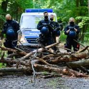 Polizisten stehen vor einer Barrikade, die Aktivisten im besetzten Waldgebiet am Montag errichtet haben.