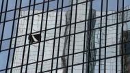 Die Zentrale der Deutschen Bank in Frankfurt spiegelt sich in den Fenstern eines Hochhauses.