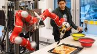Auch das ist Informatik: Ein Roboter am Forschungsinstitut Artificial Intelligence (AI) an der Universität Bremen belegt einen Pizzateig mit Käse (Archivbild aus dem Jahr 2017)