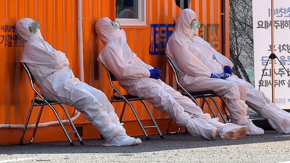 Medizinisches Personal in Schutzanzügen ruht sich vor einer Testklinik in der südkoreanischen Hauptstadt Seoul aus.