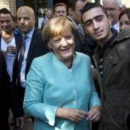 Dokumentation eines bevölkerungspolitischen Experiments? Angela Merkel besucht eine Außenstelle des Bundesamts für Migration und Flüchtlinge.