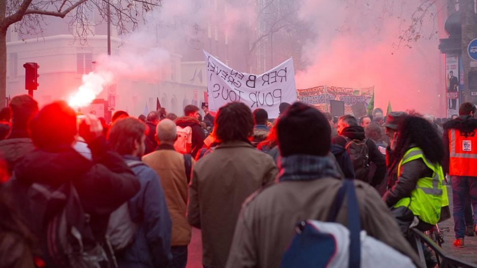 In Paris protestieren im Dezember Demonstranten mit Leuchtfackeln und Plakaten gegen die geplante Rentenreform.