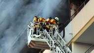 Feuerwehrleute löschen den Brand in einem Hochhaus in Stutensee bei Karlsruhe.