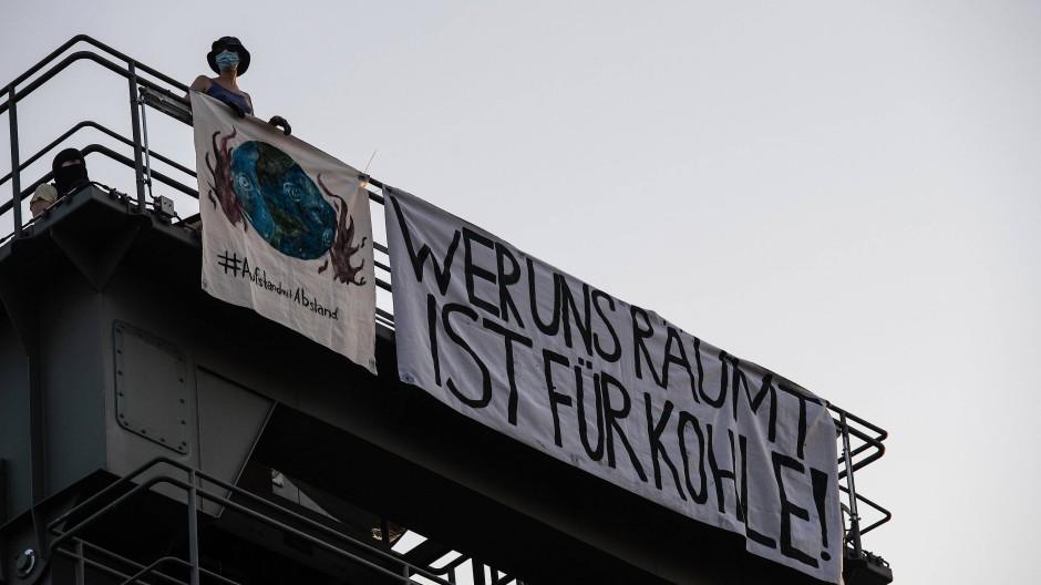 Auf dem Kraftwerksturm in Berlin-Moabit entrollten die Demonstranten ein Transparent mit der Aufschrift Wer uns räumt, ist für Kohle!