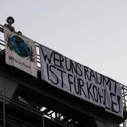 """Auf dem Kraftwerksturm in Berlin-Moabit entrollten die Demonstranten ein Transparent mit der Aufschrift """"Wer uns räumt, ist für Kohle!"""""""