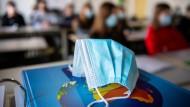 Ein Mund- und Nasentschutz liegt im Unterricht in der Jahrgangsstufe elf am staatlichen Gymnasium Trudering in München auf einem Weltatlas.