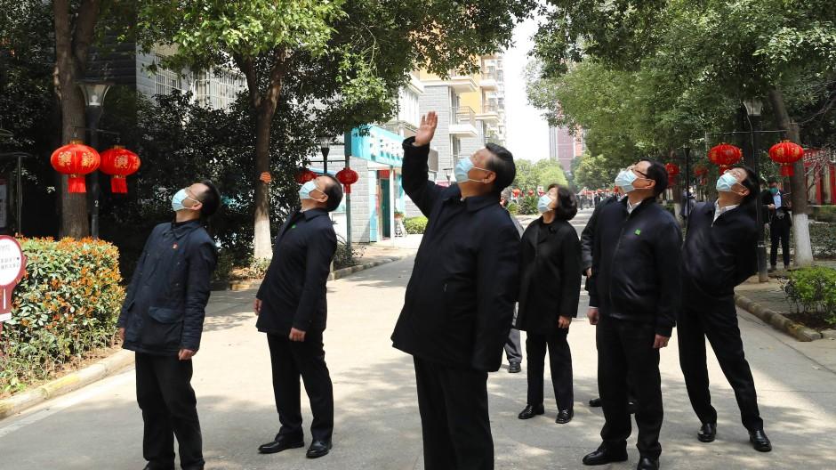 Chinas Staats- und Parteichef Xi Jinping winkt unter Quarantäne stehenden Bewohnern der Stadt Wuhan bei einem Besuch Mitte März zu.