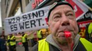 Demonstranten aus der Geld - und Werttransportbranche stehen vor der dem Gebäude im dem die Arbeitgeber- und Arbeitnehmervertreter über neue Tarife verhandeln.