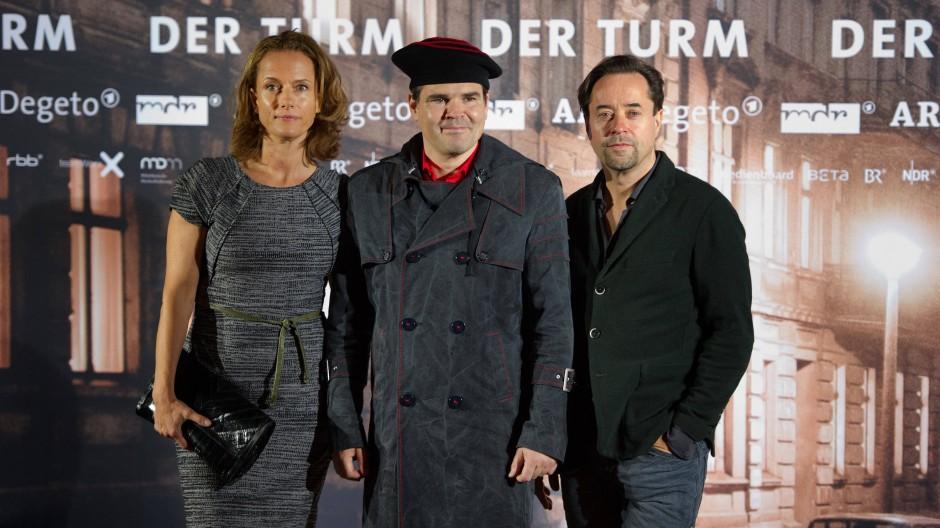 """Die  Schauspieler Claudia Michelsen und Jan Josef Liefers nehmen bei der Premiere des Fernsehfilms """"Der Turm"""" den Autor Uwe Tellkamp in ihre Mitte."""