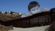 Der mexikanische Junge Kikito schaut über den Grenzzaun herüber zu den Vereinigten Staaten.