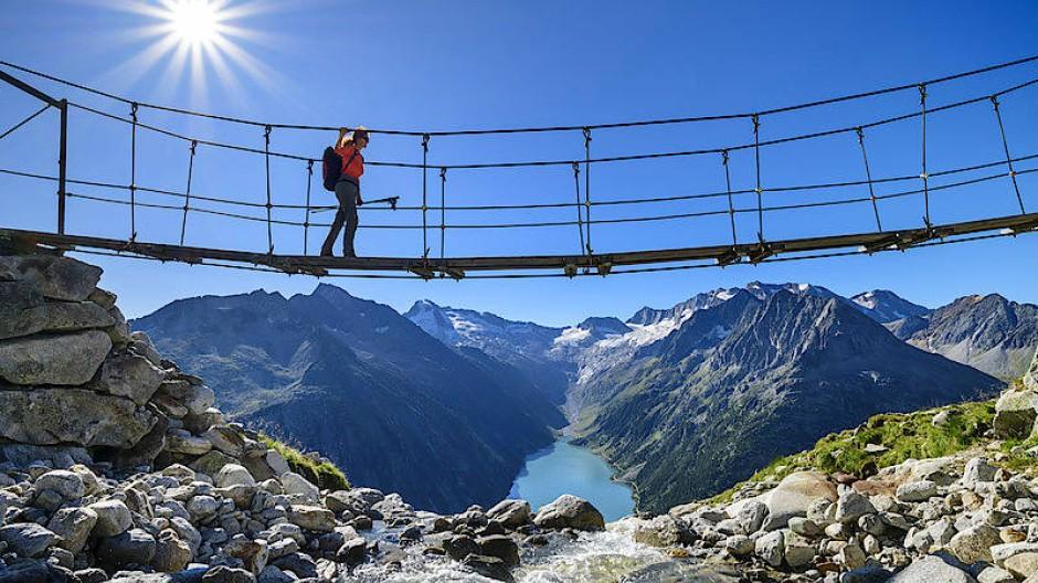 Urlauberin in den Bergen: Wer auf das Sterne-Hotel verzichtet, schafft es früher in die finanzielle Unabhängigkeit, sagt Frugalist Florian Wagner.