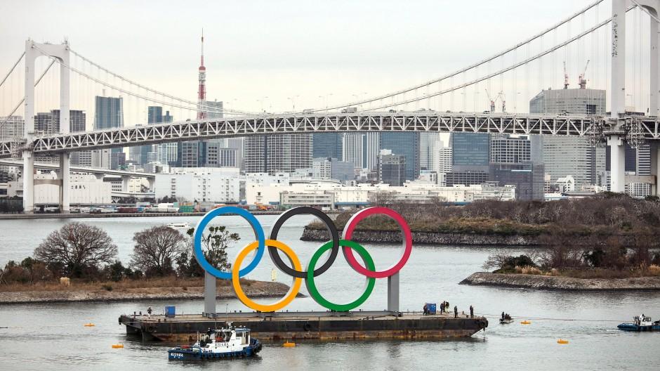 Übergroße Olympischen Ringe werden auf einem Ponton vor der Rainbow Bridge Hängebrücke im Hafen vom Odaiba Marine Park transportiert.