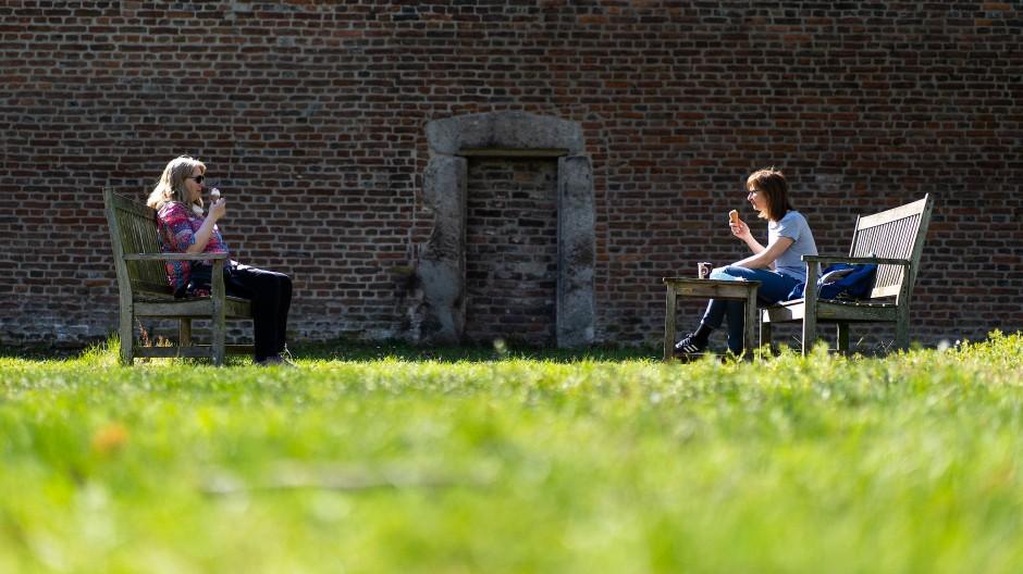 Zwei Frauen sitzen sich in Zons in NRW auf zwei Bänken gegenüber und essen Eis.