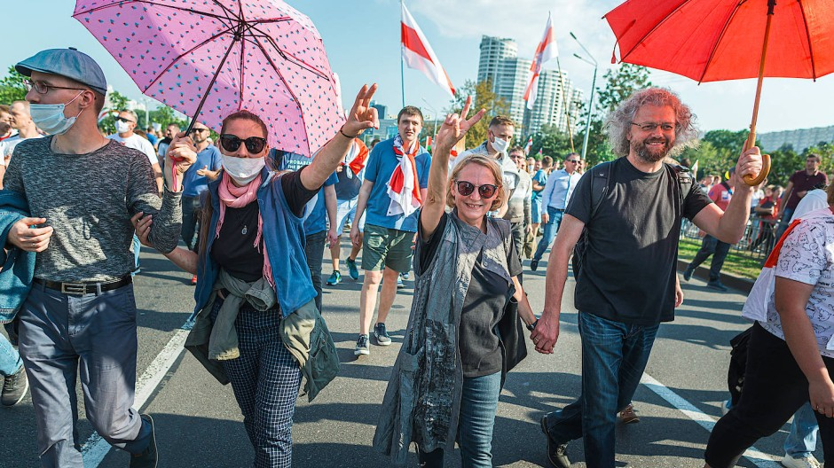 Endlich protestiert die Mehrheit: Dmitri Strozew (rechts mit Schirm) und seine Frau bei einer sommerlichen Demonstration in Minsk.