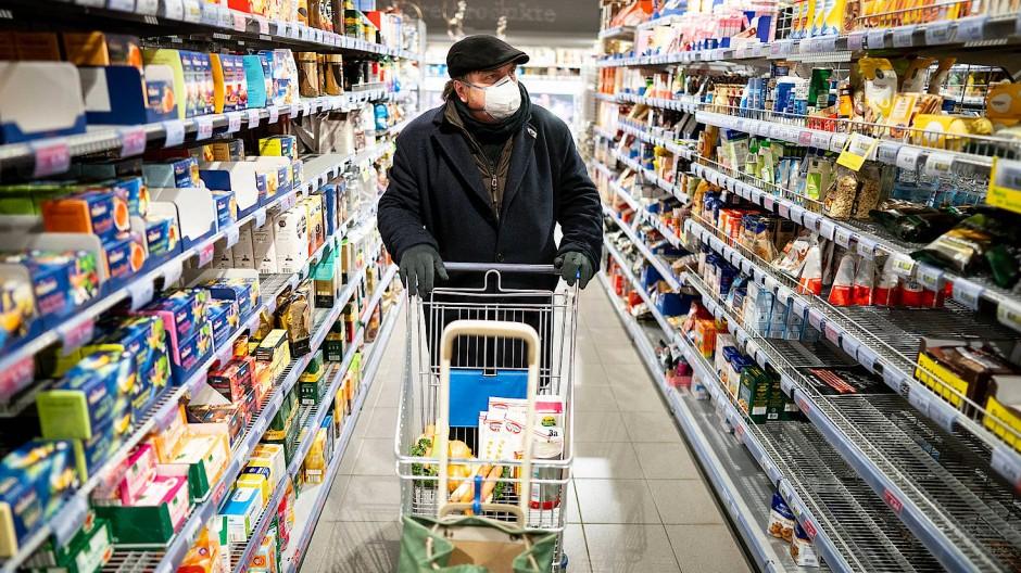 Ein Kunde kauft mit Mundschutz und Handschuhen am frühen Morgen in einem Supermarkt im Berliner Stadtteil Friedenau ein.
