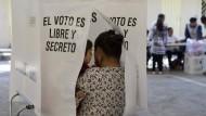 """Eine Frau, mit ihrem Kind auf den Arm, wählt  in einem Wahllokal in Ecatepec (Mexiko) hinter einem Vorgang mit der Aufschrift """"Die Wahl ist frei und geheim."""""""