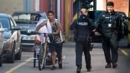 Eskorte: Polizisten geleiten einen Bewohner des Lagers vom Gelände der Firma Ferro.