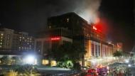 Nach dem Raubüberfall am 2.Juni steigt Rauch aus dem Hotelkomplex in der philippinischen Hauptstadt Manila
