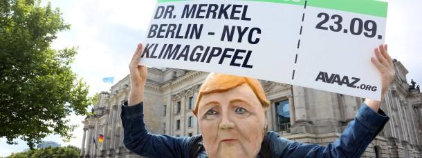 Protest für mehr Klimaschutz: Ein als Bundeskanzlerin Merkel verkleideter Demonstrant hält am Sonntag einen Boardingpass in den Händen.