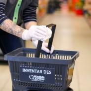 """Schutz vor Ansteckung: Eine Mitarbeiterin eines """"Konsum""""-Supermarktes desinfiziert in Leipzig die Henkel von Einkaufskörben."""