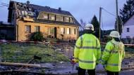 Tornado in der Eifel: Die Feuerwehr steht vor einem Haus, dessen Dach schwer beschädigt wurde.