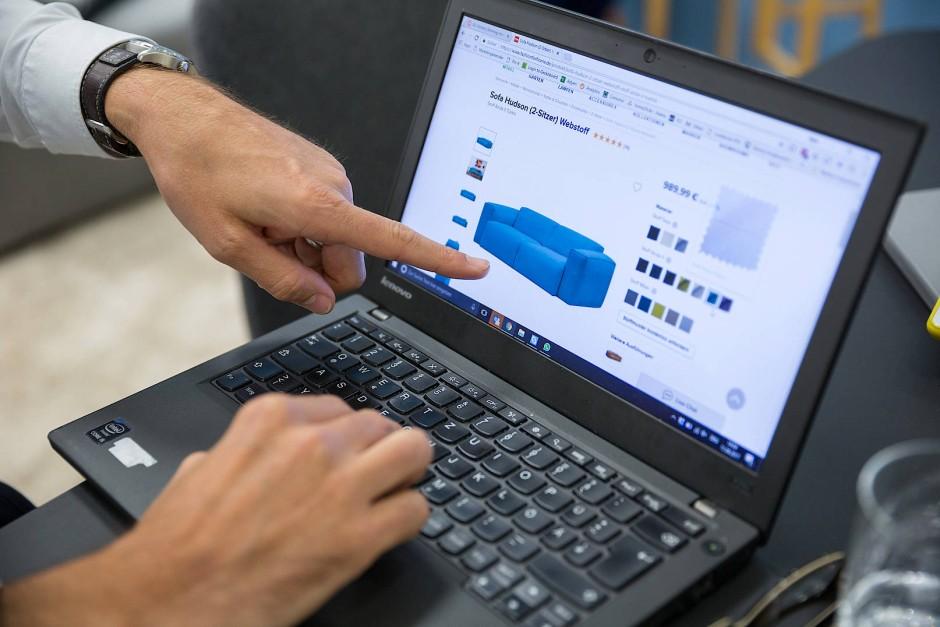 Marc Appelhoff zeigt auf seinem Laptop die Funktionsweise des Onlineshops.