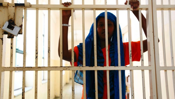 An Somali would-be immigrant looks through barred gates at the Lyster barracks detention centre for immigrants in Hal Far, outside Valletta