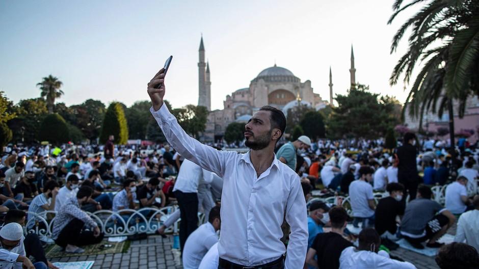 Ein Mann knipst ein Selfie von sich vor der Hagia Sophia in Istanbul.