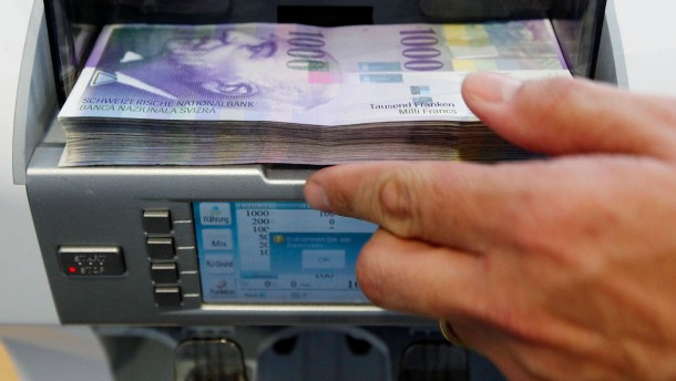 A bank clerk places1000 Swiss franc banknotes in a money counter in a Bank in Bern