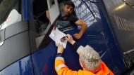 Frankreich, Coquelles: Eine Mitarbeiterin kontrolliert die Dokumente eines Lkw-Fahrers im Eurotunnel-Terminal.