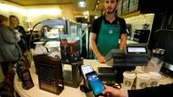 Ein Mann bezahlt im Oktober 2016 in Moskau mit dem Bezahldienst Apple Pay