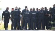 Polizeibeamte warten mit Stöcken in den Händen auf einem Feldweg nahe Wiesbaden-Erbenheim auf ihren Einsatz.