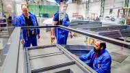 Mitarbeiter von Glasbau Hahn fertigen eine Vitrine für ein Museum im Ausland.