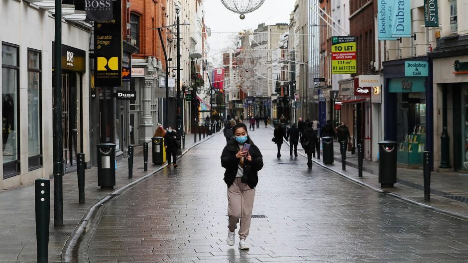 Nur wenige Passanten sind in der Dubliner Innenstadt unterwegs. Das öffentliche Leben ist dort zunächst bis Ende Januar weitgehend heruntergefahren worden.