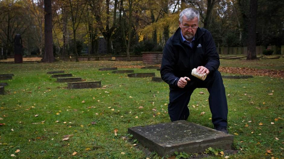 """Der Angehörige Gerhard von Hasseln entzündet ein Grablicht auf dem Ehrenfeld für """"Euthanasie""""-Opfer auf dem Frankfurter Hauptfriedhof. (Archivbild)"""